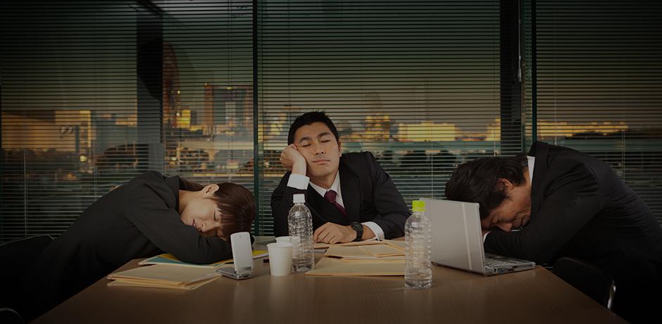 オフィスで疲れて眠る人々